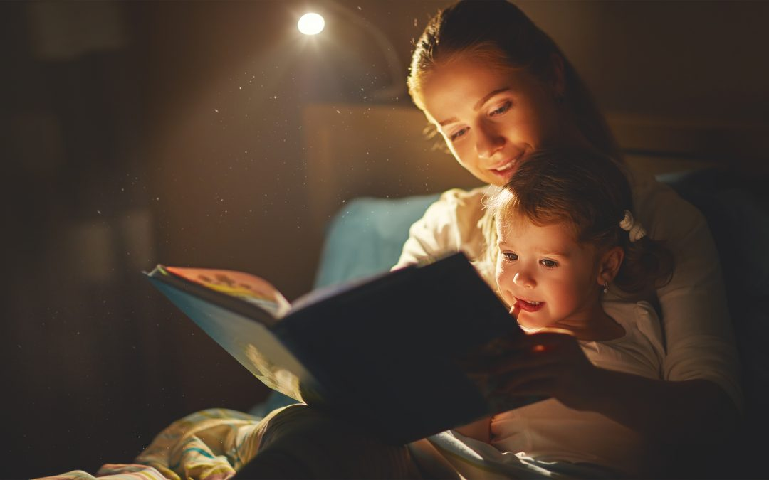 mother and daughter reading a book in bed before going to sleep